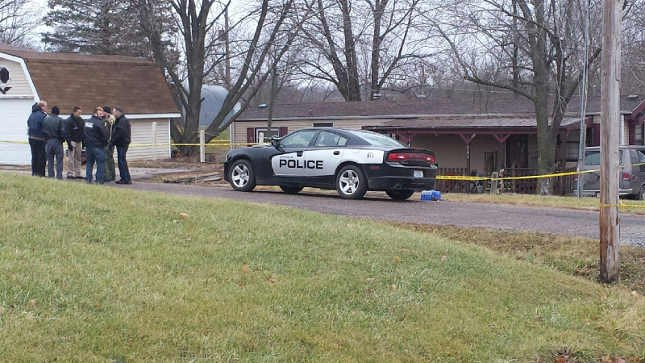 Authorities gather outside Warsaw home Wednesday.