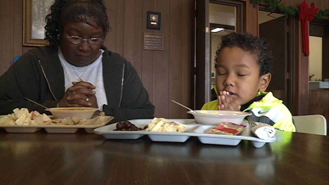 Renice Cobb Mallory and her grandson say their prayers before lunch at Horizons.