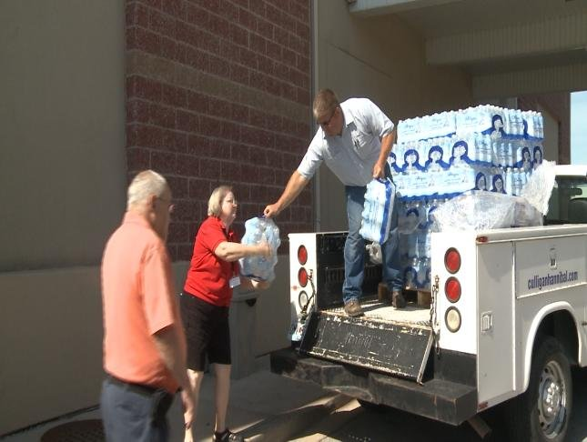 An employee of Culligan Water hands cases of water to people waiting to take them to Quincy residents.