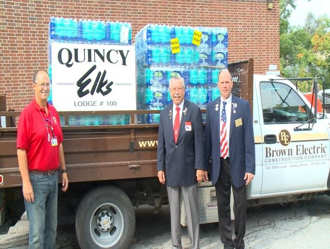Three men stand in front of the water donated to the veterans home.