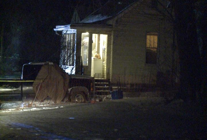 A pickup parks outside a house where a woman was found shot to death Tuesday evening.