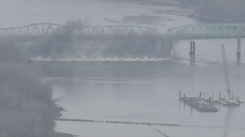 The old Daniel Boone Bridge hits the water of the Missouri River after MoDOT blew it up Thursday morning