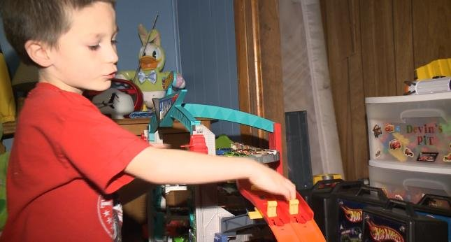 Devin Ryan, now a playful kid, shows off some of his toys.