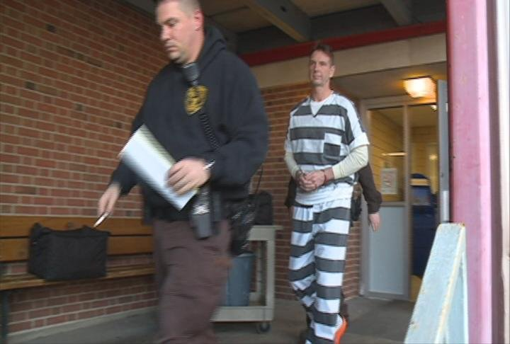 Authorities lead Curtis Lovelace to a transport van before a court appearance