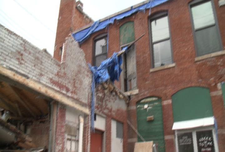 The old Greek To Me building at 6th and Hampshire still sits with a shredded tarp and crumbling walls a year after being damaged in last July's windstorm