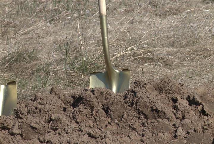 Officials breaking ground with golden shovels