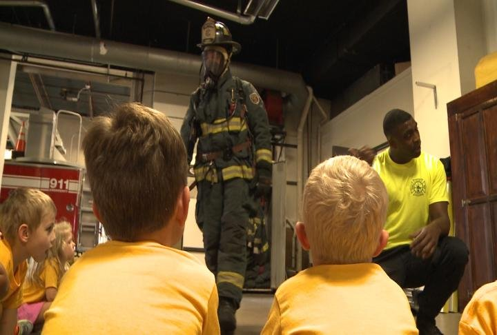 Children look on at a firefighter in his gear.
