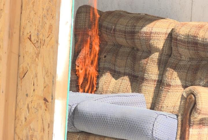 Fire spreads up a couch.