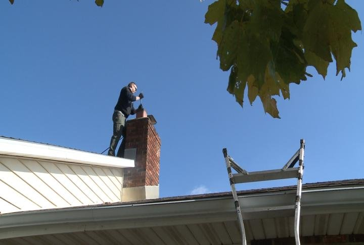 Cole Miller sweeping a chimney.