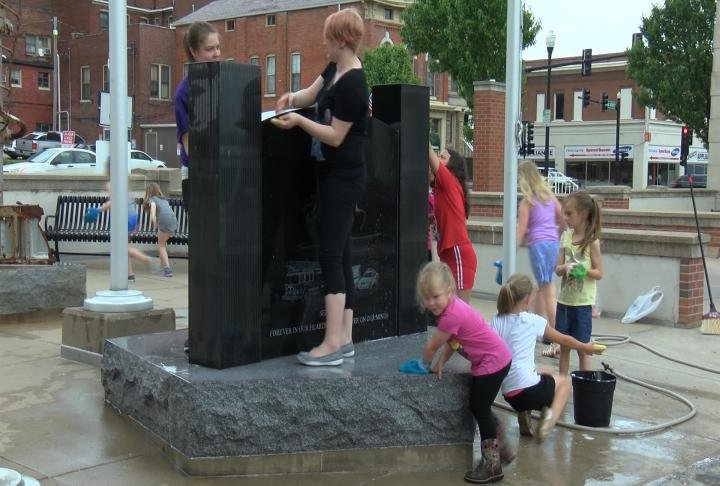 Quincy Girl Scouts clean World Trade Center monument outside Quincy City Hall Tuesday afternoon.