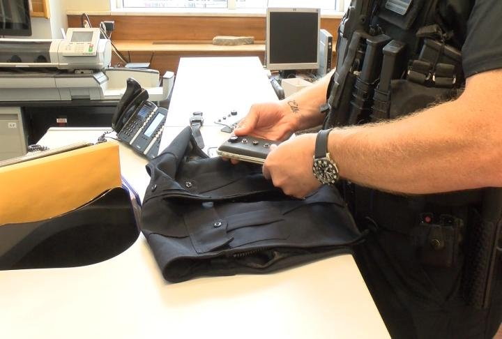 A Quincy police officer examines a new body camera from the company Bodyworn