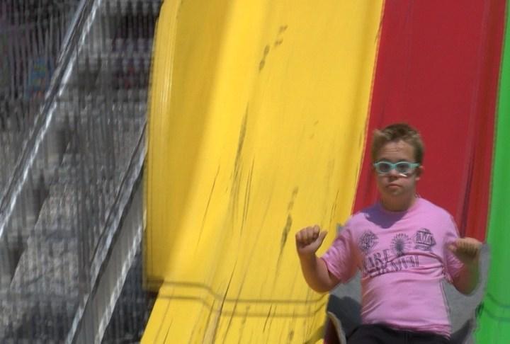 A boy rides down carpet slide